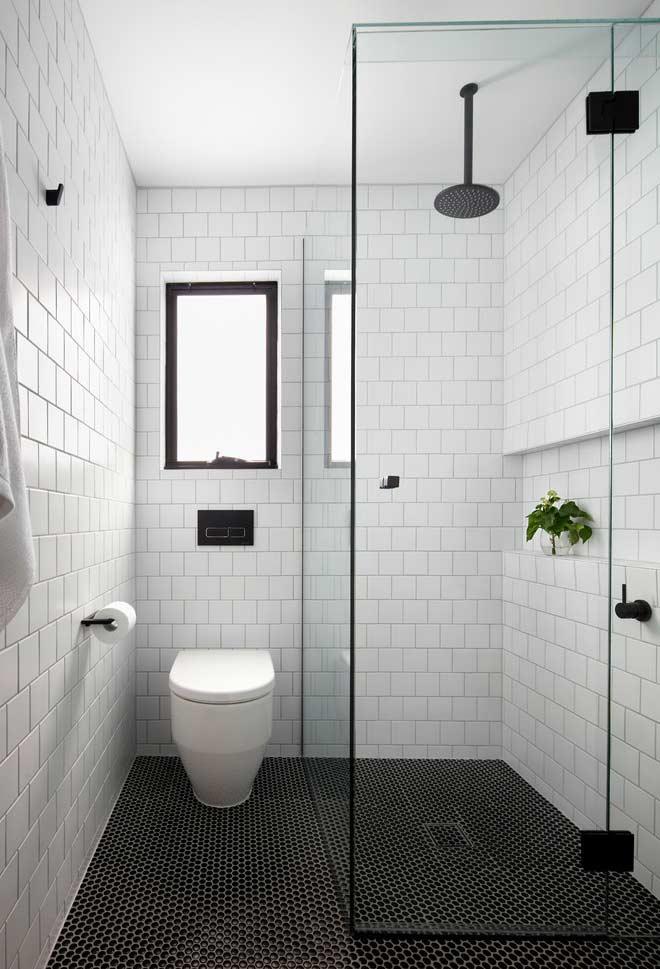 Banheiro branco e preto com azulejo preto.