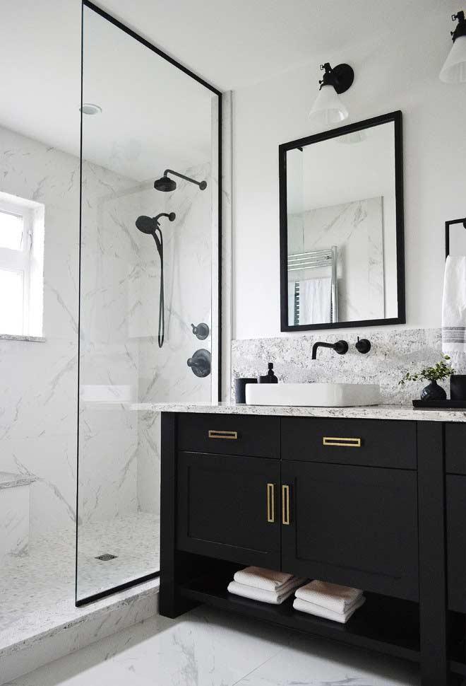 Banheiro branco e preto com armário preto e revestimento de porcelanato.