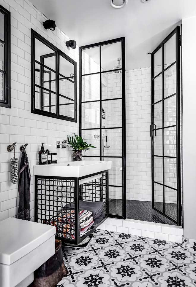 Banheiro branco e preto com metais pretos e ladrilho hidráulico.