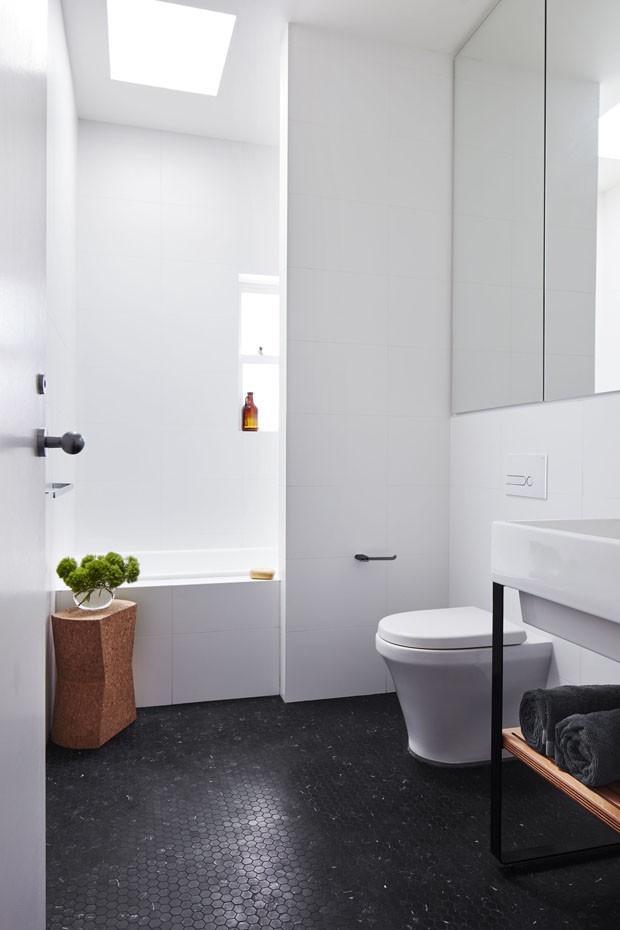 Banheiro branco e preto moderno com piso preto e vaso de planta.