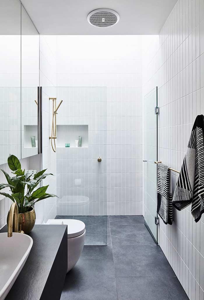 Banheiro branco e cinza com piso cinza.