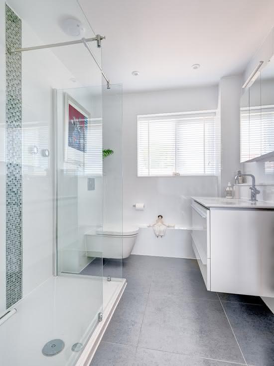Banheiro branco e cinza com vaso suspenso.