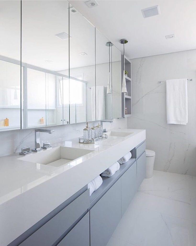 Banheiro branco e cinza com bancada dupla e decoração luxuosa.