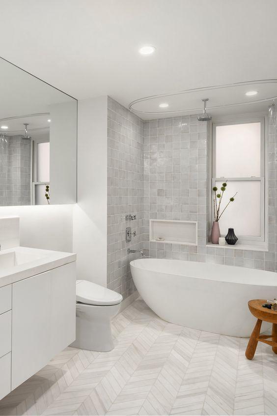 Banheiro branco e cinza com banheira moderna.