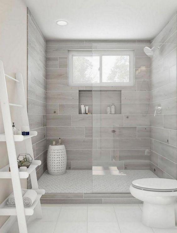 Banheiro branco e cinza com revestimento que imita madeira.