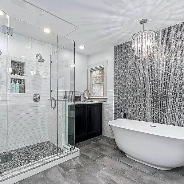 Banheiro branco e cinza luxuoso com pastilha metalizada e lustre.