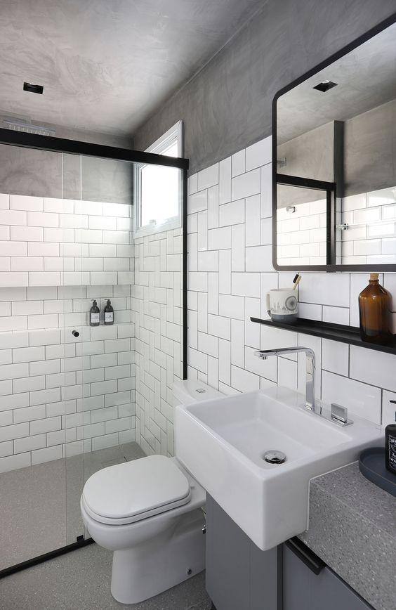 Banheiro branco e cinza com azulejo metro white e parede de cimento queimado.
