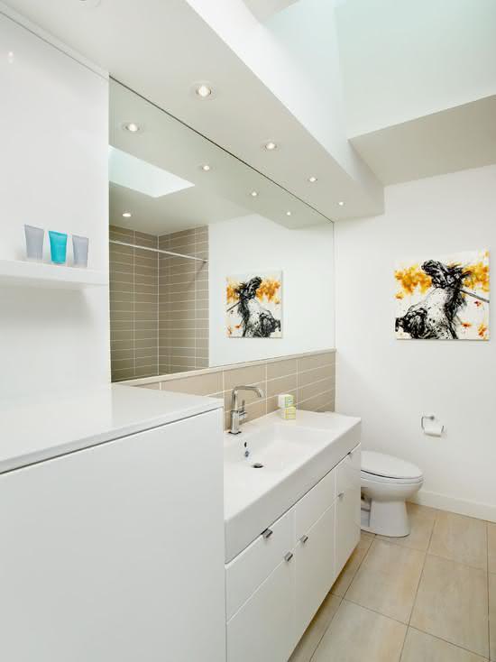 Banheiro branco com revestimento bege.
