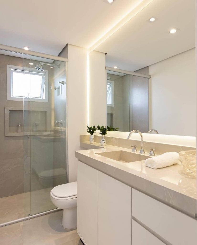 Banheiro branco com pia esculpida bege.