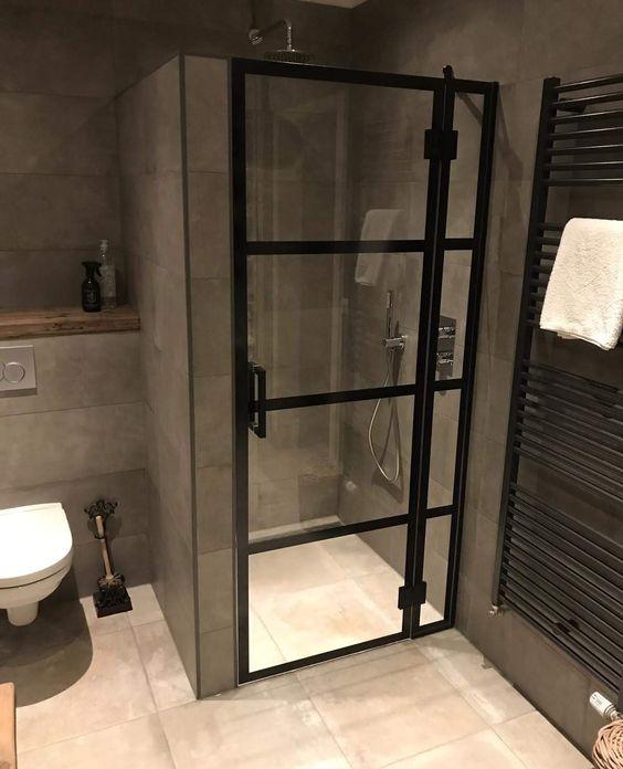 box de banheiro com porta de vidro e metal