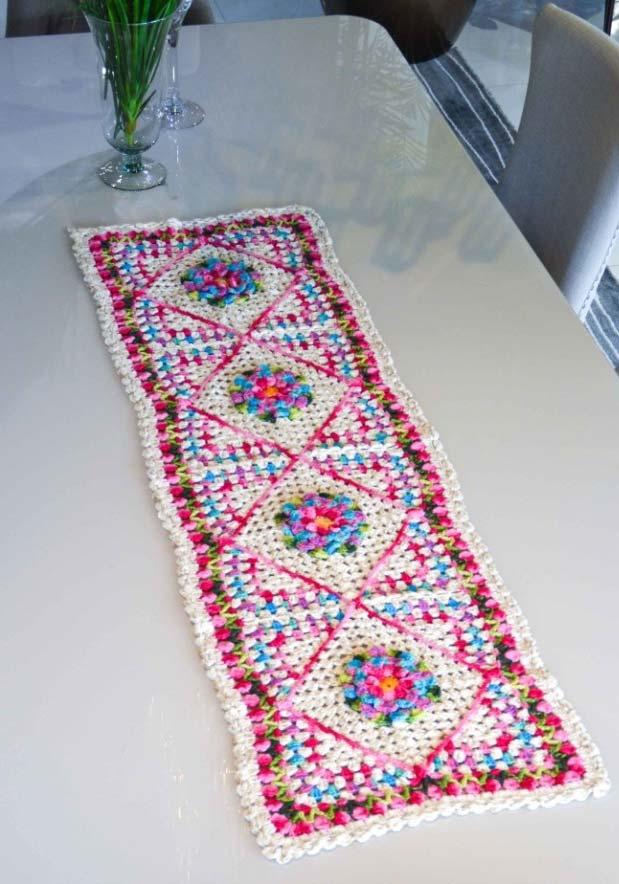 Caminho de mesa de crochê com bordado colorido.