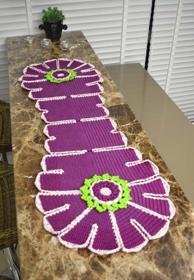 Bancada de mármore com caminho de mesa de crochê roxo.