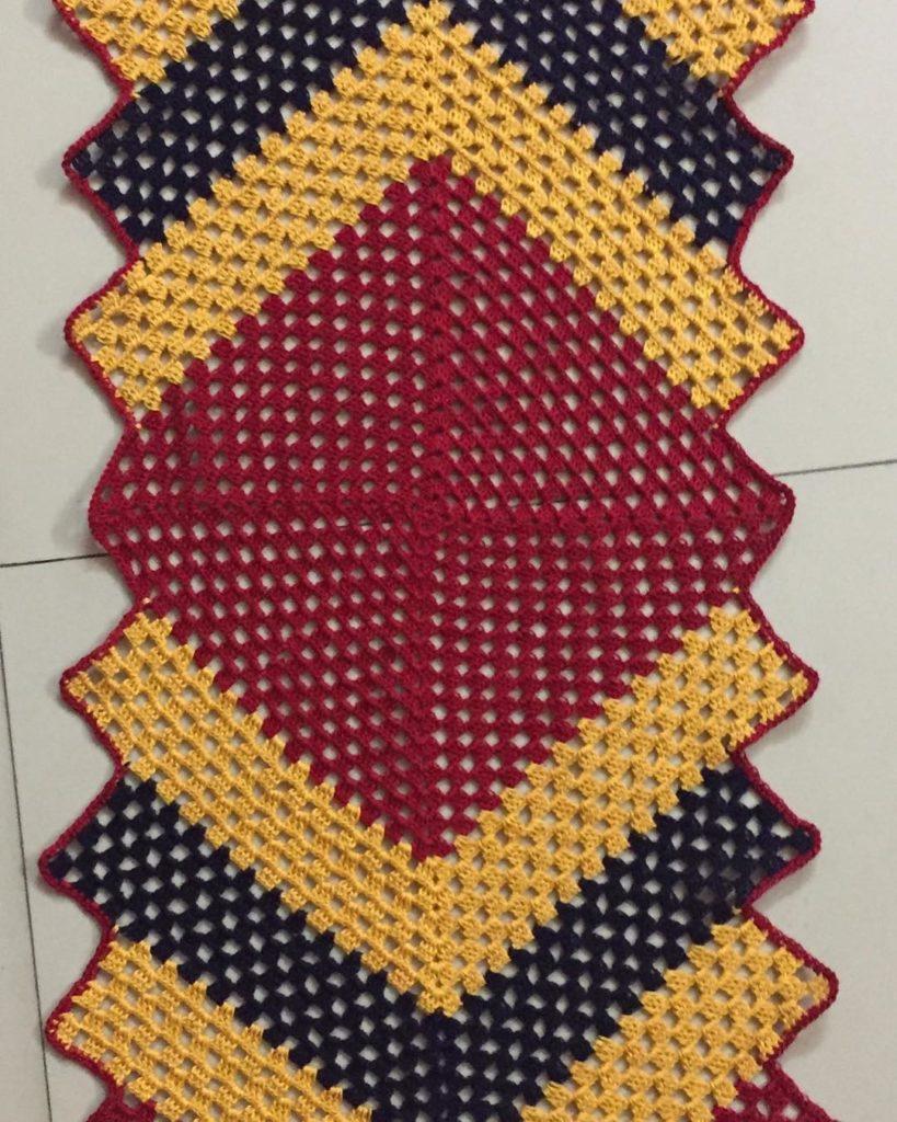 Caminho de mesa de crochê colorido com vermelho, amarelo e preto.