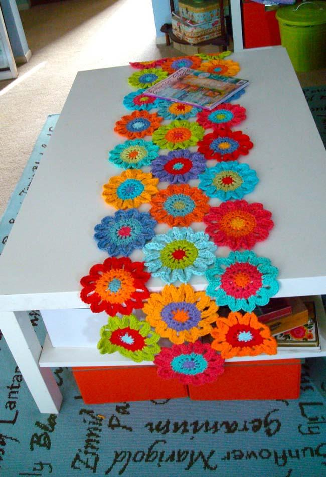 Caminho de mesa de crochê com flores coloridas.