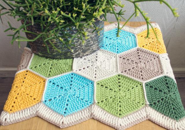 Caminho de mesa de crochê com forma geométrica.