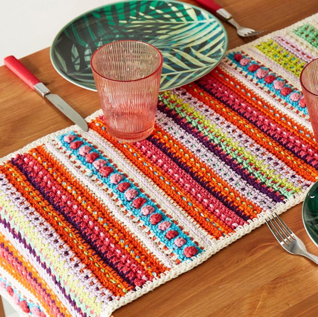 Caminho de mesa de crochê colorida e retangular.