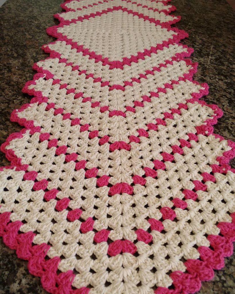 Caminho de mesa de crochê branco e rosa.