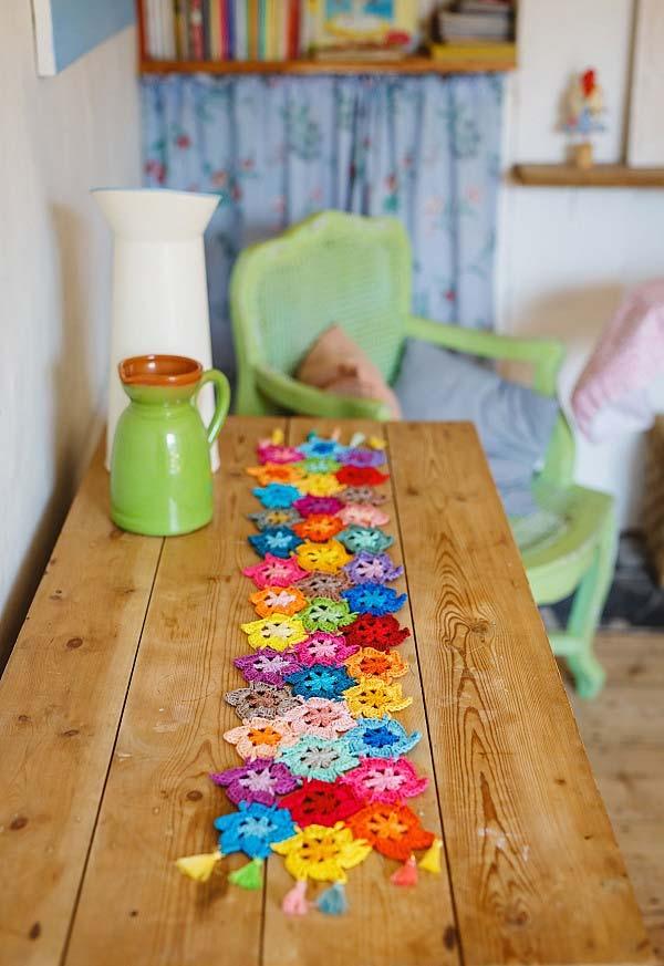 Caminho de mesa de crochê pequeno com flores coloridas.