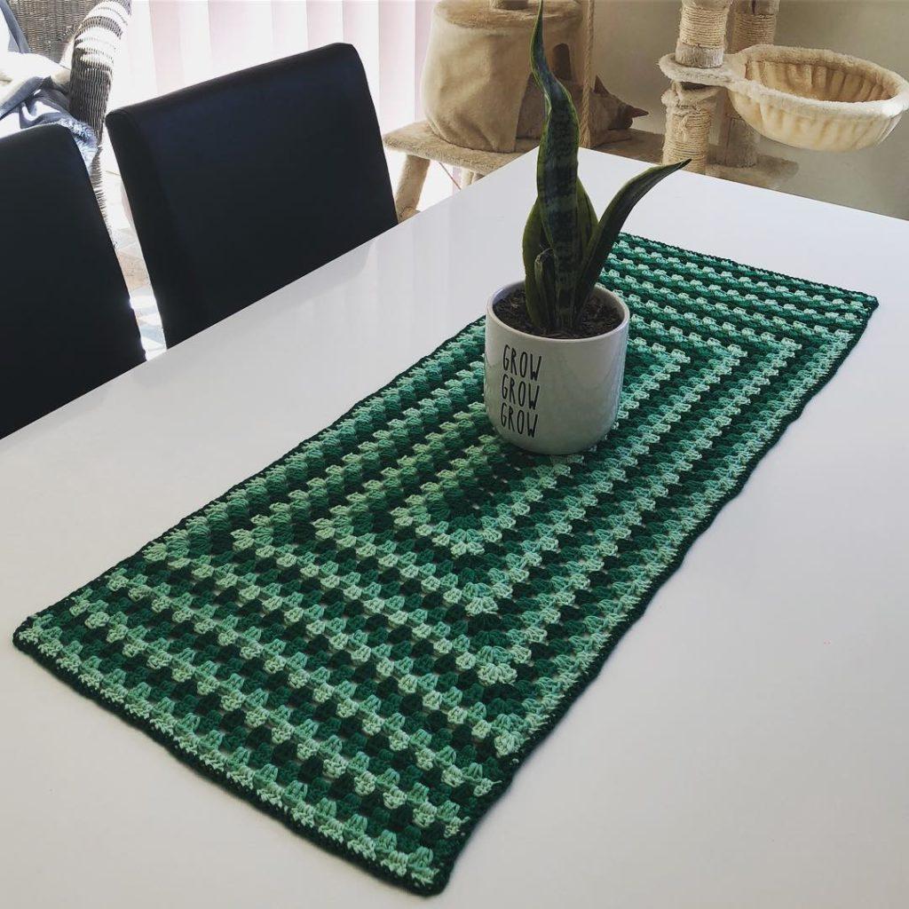 Mesa decorada com toalha simples e verde.