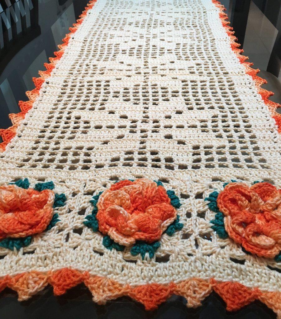 Mesa com decoração branca com bico laranja e flores.