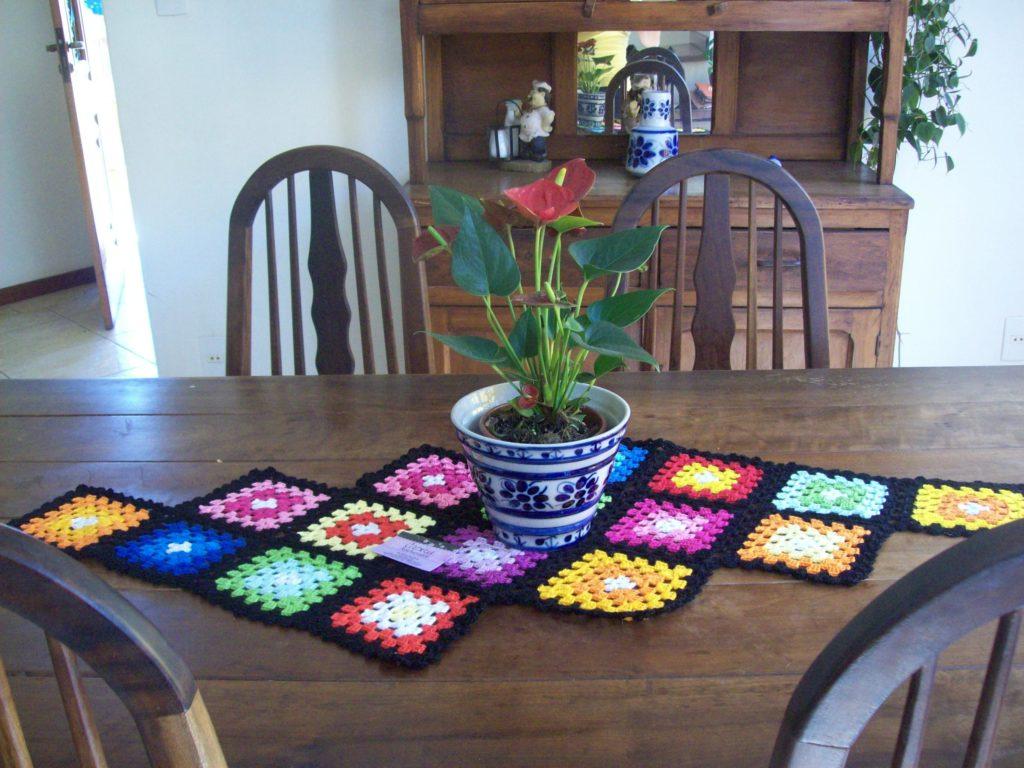 Caminho de mesa de crochê colorido com formato quadrado.