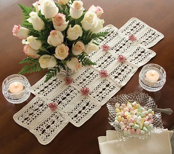 Caminho de mesa de crochê com flores rosas.
