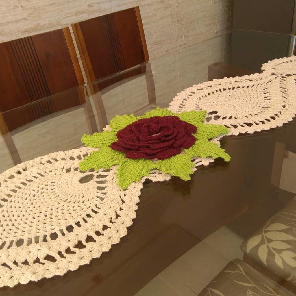 Caminho de mesa de crochê branca com flor gigante.