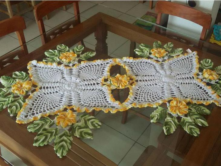 Caminho de mesa de crochê com flores amarelas e folhas.