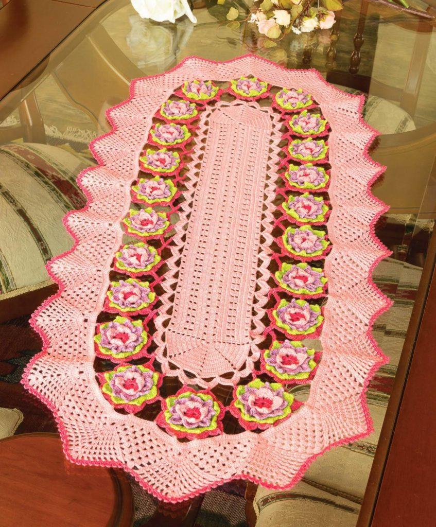 Caminho de mesa de crochê rosa com flores.
