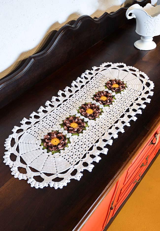 Caminho de mesa de crochê branca com flores no centro.