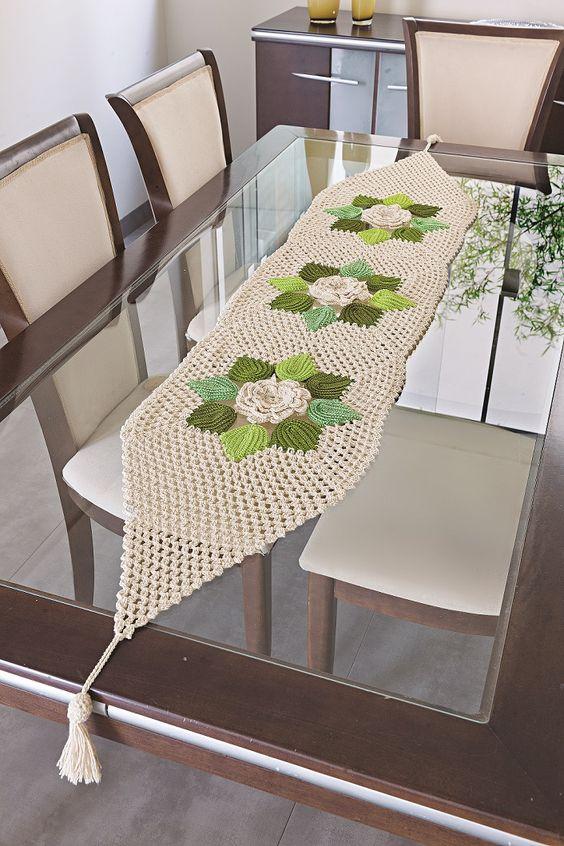 Caminho de mesa de crochê de barbante com flores no centro.