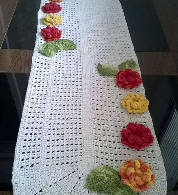 Caminho de mesa de crochê branca com flores.