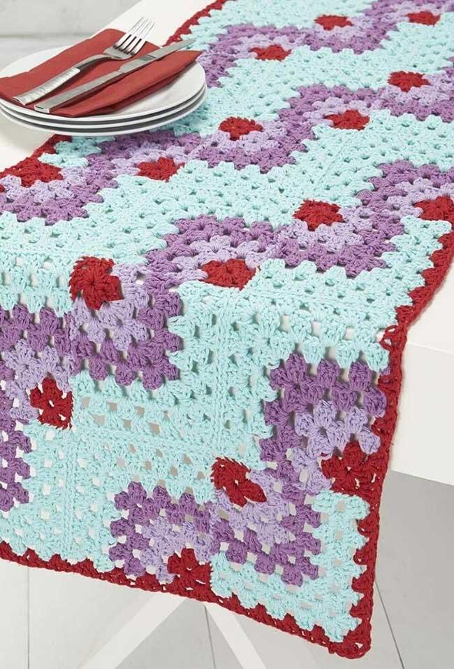 Caminho de mesa de crochê azul, roxo e vermelho.