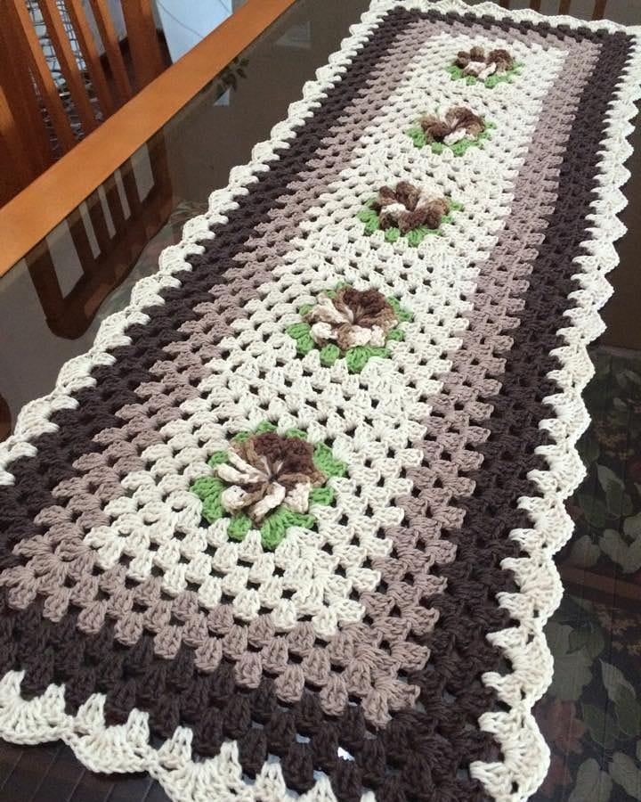 Caminho de mesa de crochê roxo e branco.