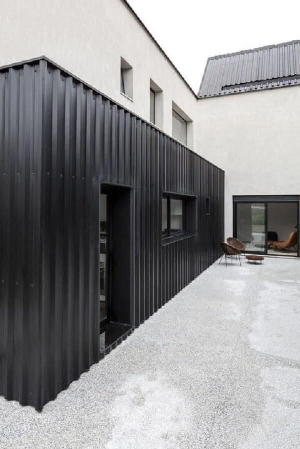 Casa branca de concreto e container preto.