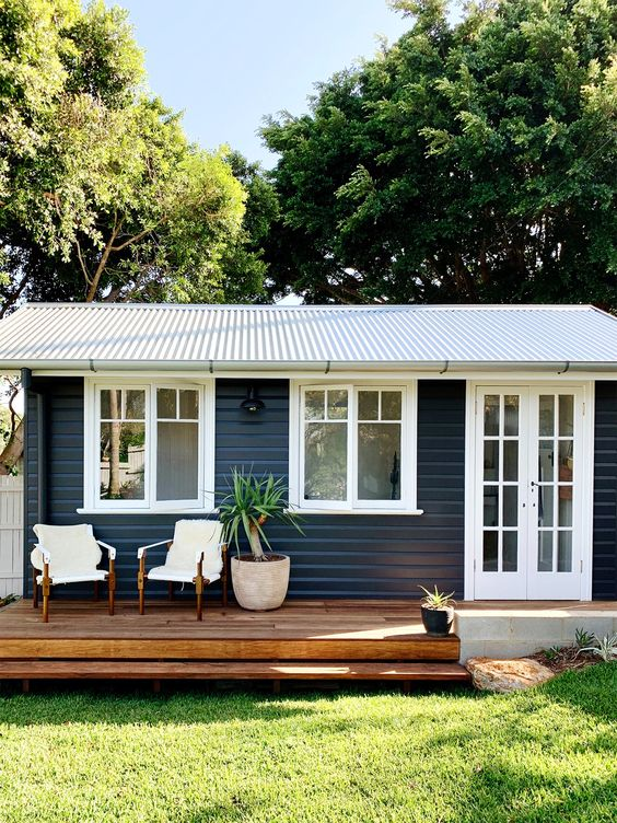 Casa com deck de madeira e duas cadeiras.