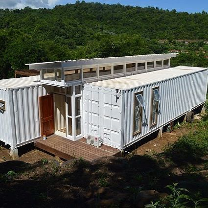 Casa container branca no meio da floresta.