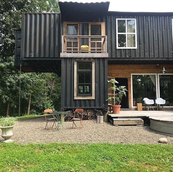 Casa preta com deatlhe de madeira.