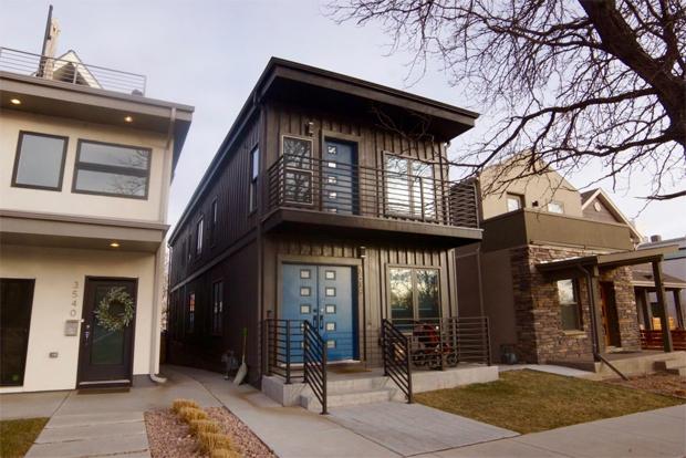 Casa preta com varanda.