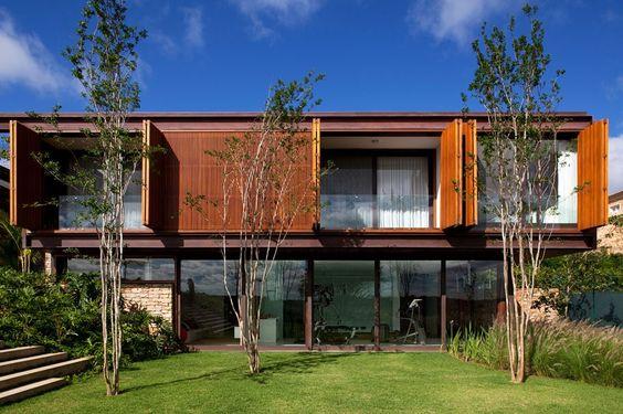 Casa container com vidro e gramado na frente.
