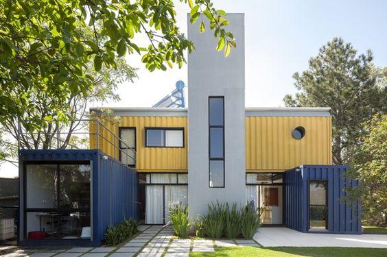Casa grande de containers azul, amarelo e cinza.