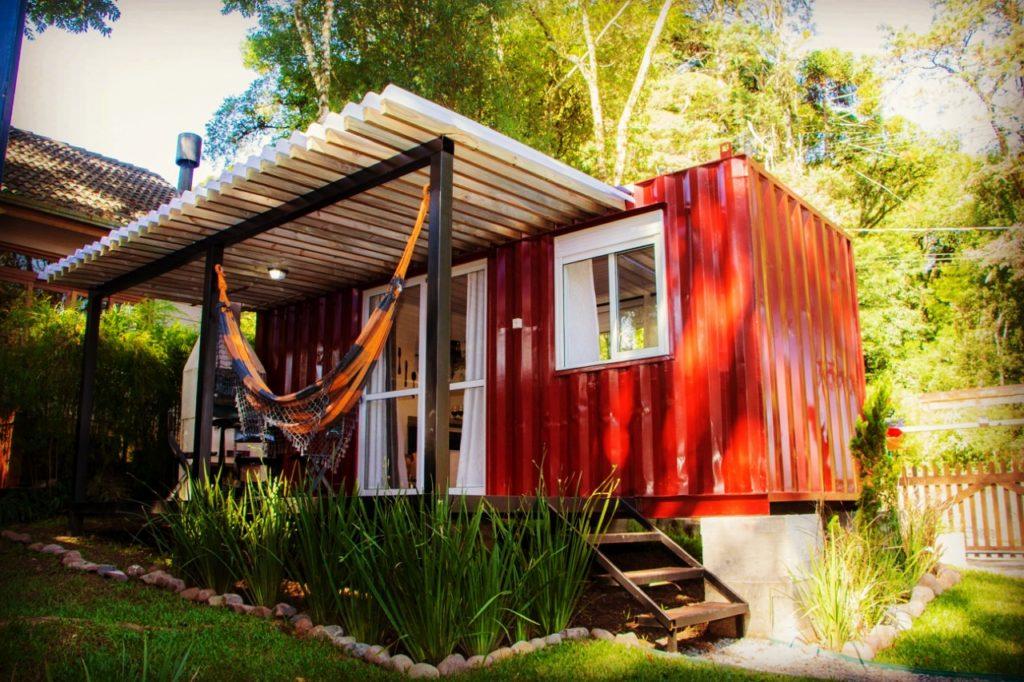 Pequena casa vermelha com churrasqueira e rede.