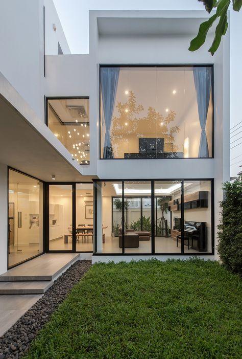 Casa branca com grande área de vidro.