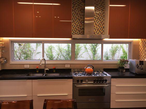 Cozinha com janela entre o armário e a pia.