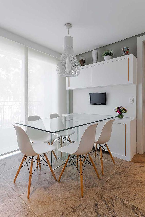 Sala de jantar com mesa de vidro para cinco cadeiras.