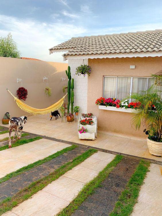 Casa pequena com vasos de flores e plantas.