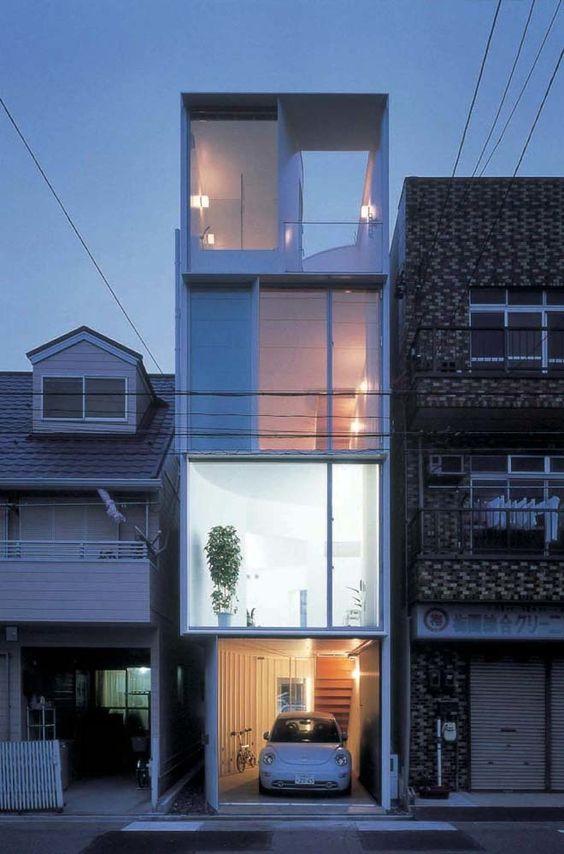 Casa estreita de três andares e carro na garagem.