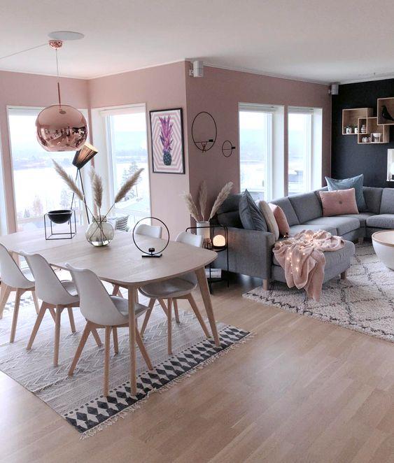 Sala com sofá cinza e almofadas rosa.