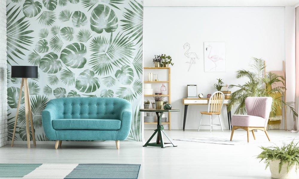Sala decorada com papel de parede com estampa de folhas.