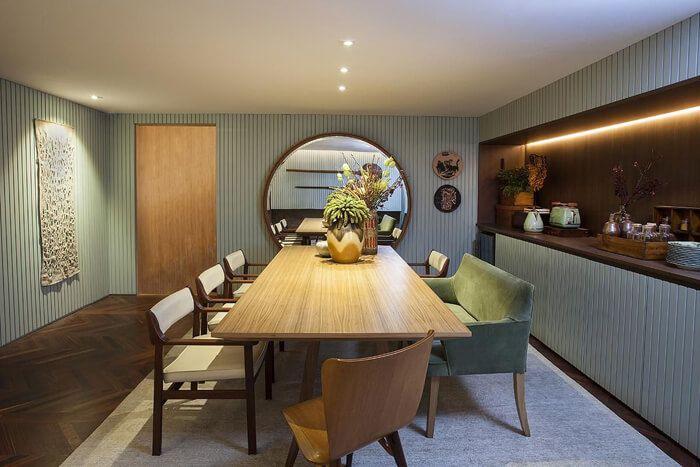Sala de jantar decorada com espelho redondo.